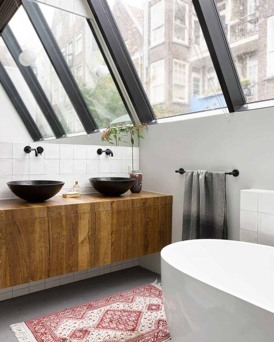 an industrial attic bathroom with white tiles, a grey floor, an oval tub, a glazed wall and a wooden vanity