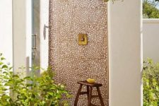 an outdoor shower with a single wall clad with pebbles and a wooden floor feels very textural and very natural