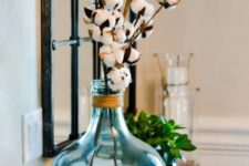 an oversized blue bottle with twine and cotton branches is a cute farmhouse-inspired decoration to rock
