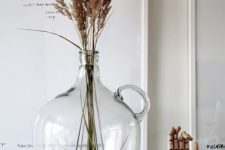an oversized bottle with dried herbs is a cool decoration to rock for any space that lacks a natural touch
