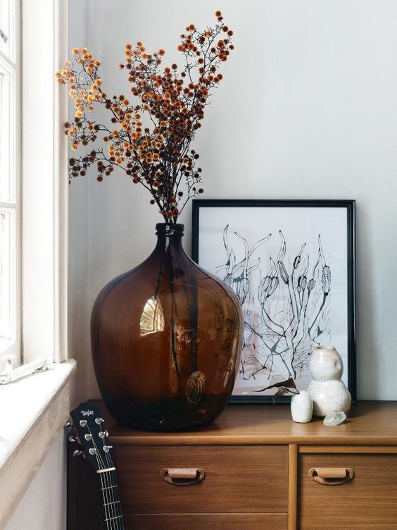 an oversized brown bottle with dried blooms is a cool decoration for any space