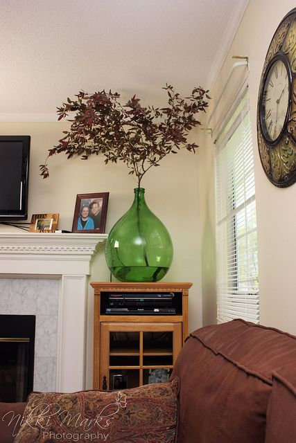 an oversized green bottle with bright leaves is a cool decoration for any space and it will bring much color