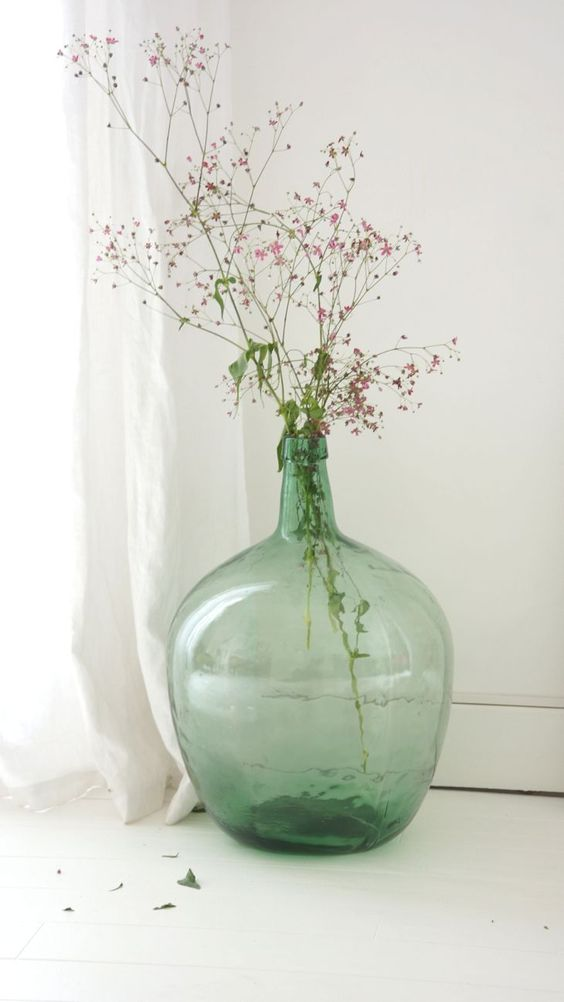 an oversized green bottle with pink blooms brings a fresh and bright feel to any space