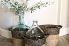 baskets with oversized bottles, with greenery and olive branches add a farmhouse feel to the space