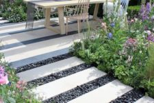 black pebbles and white stone tiles make up a chic and bold contrasting garden path with style