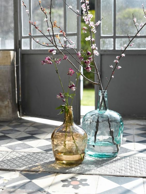 large bottles in blue and brown with blooming branches make the space fresh, bright and spring-filled
