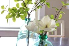oversized green bottles with leaves and neutral blooms make cool centerpieces and refresh the space