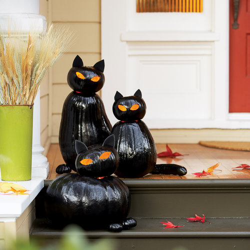 Glossy black cats could watch over trick-or-treaters at your door. The project involves pumpkin carving and spray painting but it very well worth it. (via www.sunset.com)