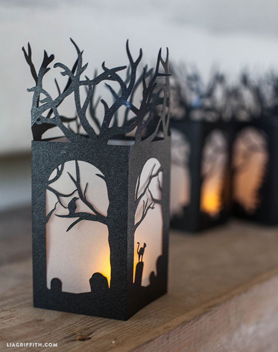 These mini lanterns are cut from a sheet of black metallic paper. A half sheet of white vellum was used to make the frosted windows. Inside are small battery operated tea lights. (via https:)
