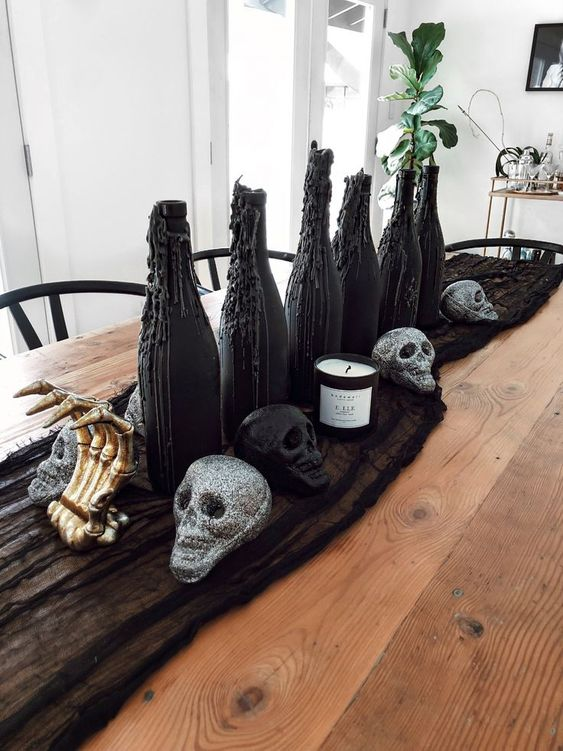 a Halloween centerpiece of black cheesecloth, glitter skulls, gilded skeleton hands, black wax bottles with greenery