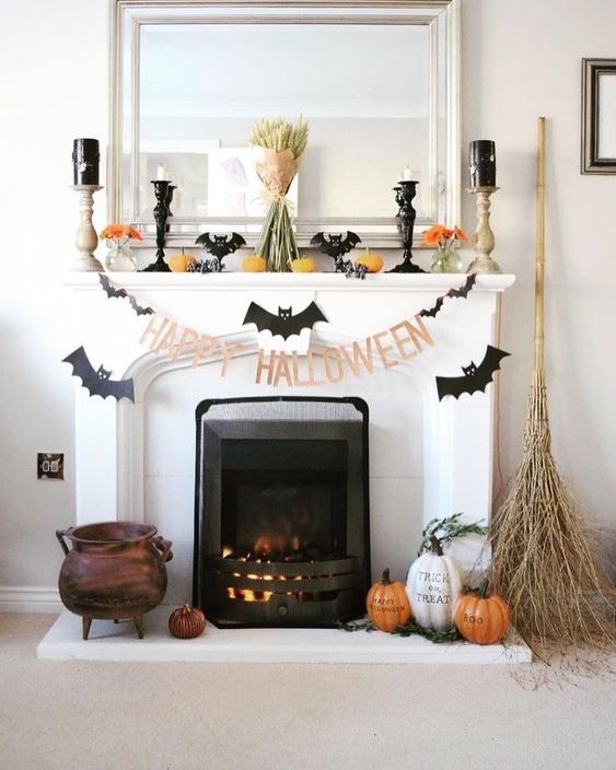 a Halloween mantel with bats, candles, pumpkins, orange blooms, a wheat bundle and some pumpkins and a broom on the floor