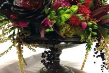 a black bowl with succulents, cascading greenery and branches, dark blooms and a sparkling red skull