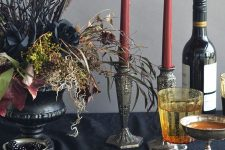 a black urn with hay, greenery, berries, grasses, black roses and black branches for a stylish Halloween tablescape
