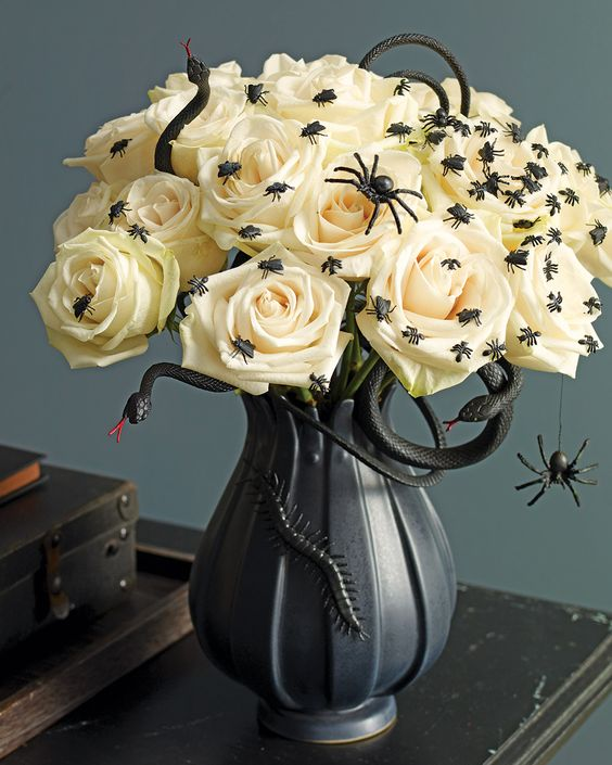 a black vase with snakes and insects, white roses topped with black spiders make up a stylish centerpiece for Halloween