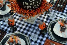 a blakc pumpkin with letters, berries on a vintage stand is ideal for a Halloween party