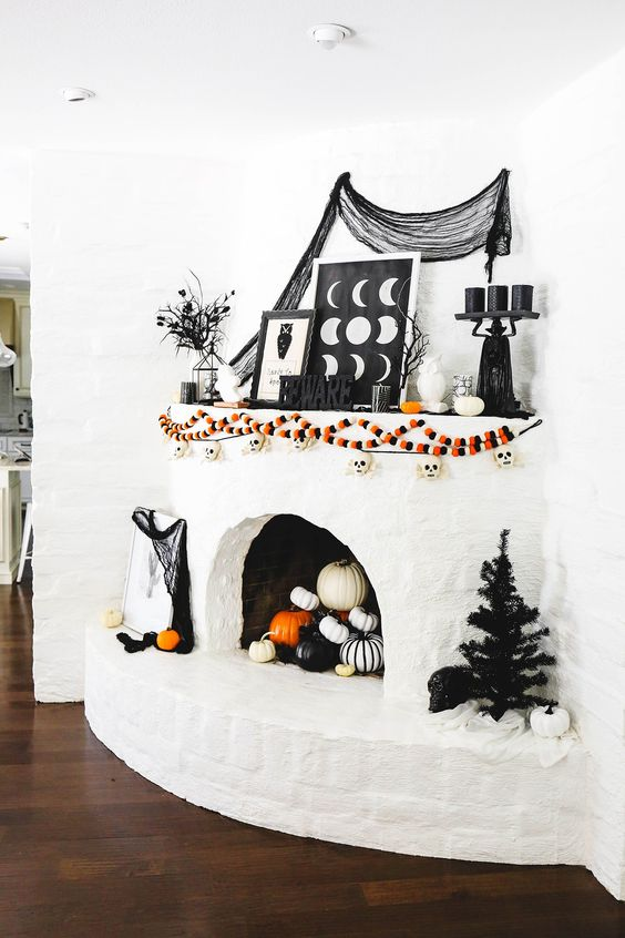 a bold Halloween mantel with colorful garlands, letters, spiderweb, black candles, branches and black and white pumpkins