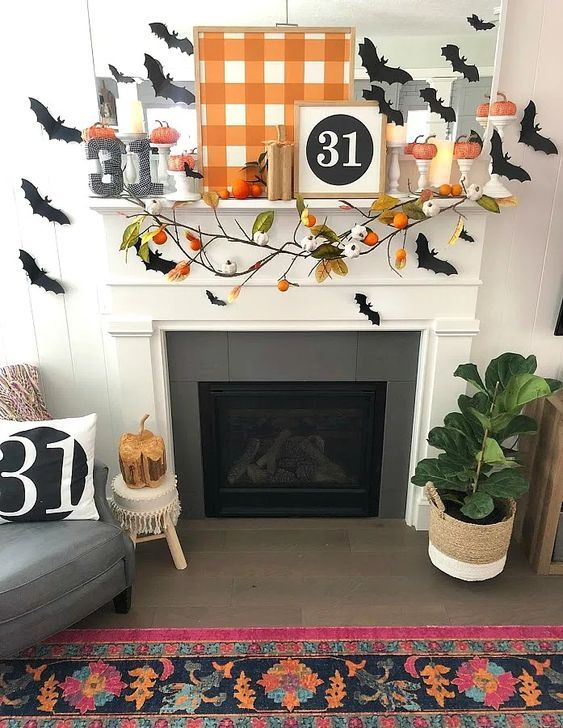 a bright Halloween mantel with a plaid sign, bats, a branch with pumpkins, mini pumpkins and candles