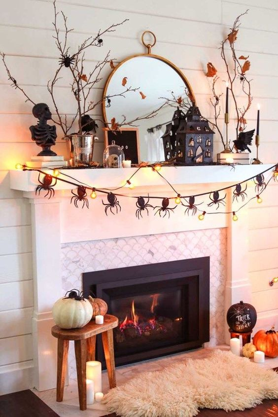 a catchy Halloween mantel with a spider garland, lights, branches with leaves, a scary house and some pumpkins on the floor