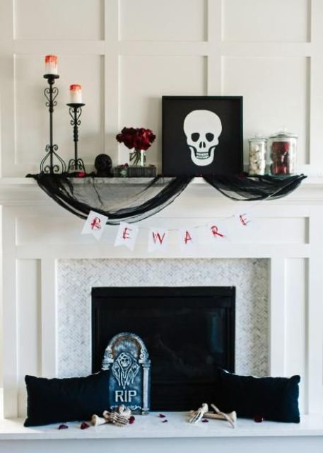 a chic Halloween mantel with bloody candles, red roses, a skull artwork, black tulle, black pillows and skeleton hands