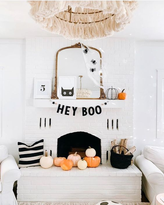 a chic Halloween mantel with spiderweb and spiders on the mirror, pumpkins, a black garland and pumpkins in the fireplace