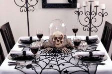 a cloche with hay, a skull, skeleton hands is a timeless Halloween decor idea to try