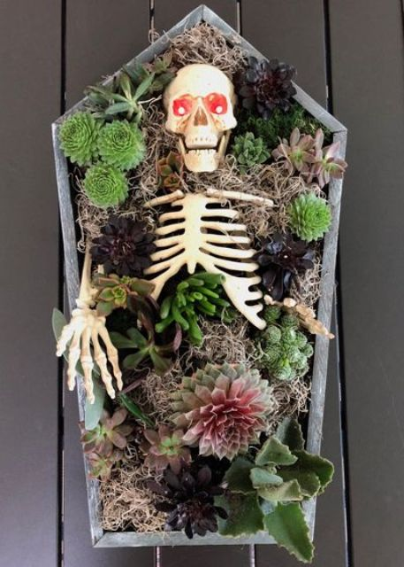 a coffin and skeleton centerpiece with succulents, moody blooms, greenery, hay and lights is a very creative idea