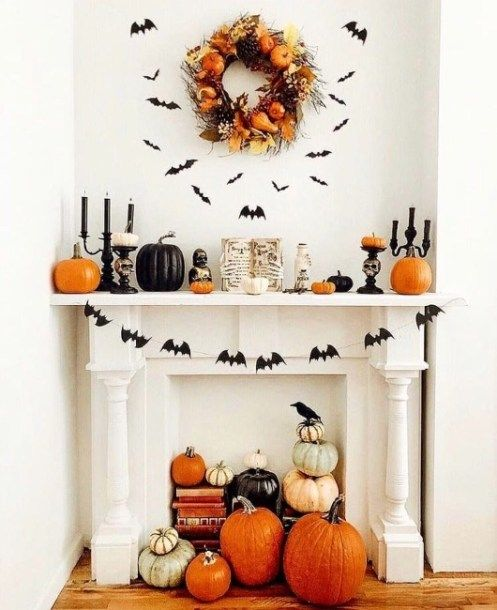 a fantastic fall and Halloween mantel with bats, a bat garland, black and orange pumpkins and black candles