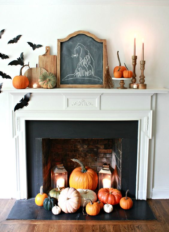 a farmhouse Halloween mantel with bats, cutting boards, candles in wooden candleholders, pumpkins all over and a witch hat sign
