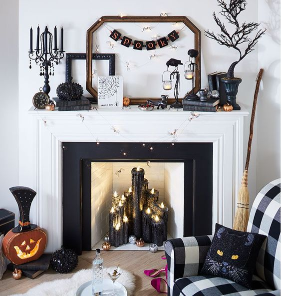 a glam Halloween mantel with black candles, a rhinestone pumpkin, a scary tree, banners, lights and a vintage clock