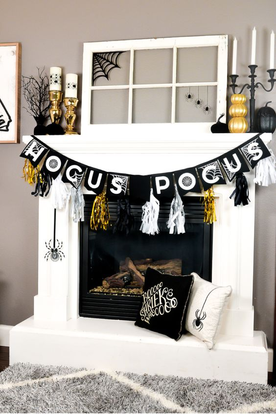 a glam Halloween mantel with gilded pumpkins, candleholders, black pumpkins, spiders and bright tassels