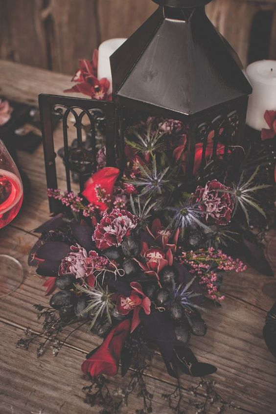 a gorgeous and sultry Halloween centerpiece of a black lantern, fuchsia and red blooms, thistles and grapes