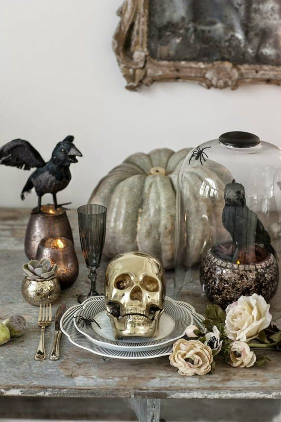a heirloom pumpkin, a crow in a cloche, blackbirds, candles in chic candleholders for Halloween