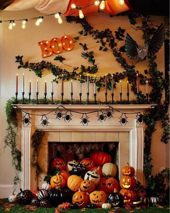 a jaw-dropping Halloween mantel with a moss garland and lots of candles, greenery on the wall, lots of colorful pumpkins and jack-o-lanterns in the fireplace