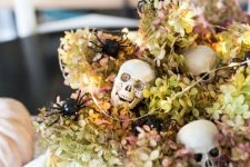 a neutral bowl with dried hydrangeas, skulls, lights and white velvet pumpkins for Halloween