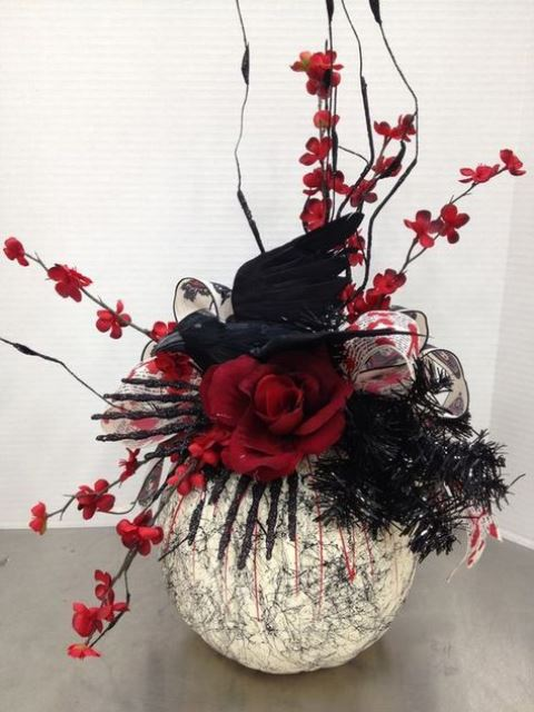 a painted pumkin with red blooms, a crow, a ribbon and black bottle cleaners are a great Halloween centerpiece