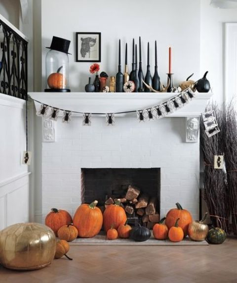 a refined Halloween mantel with black and orange candles, a bug garland a top hat, various pumpkins and black bottles