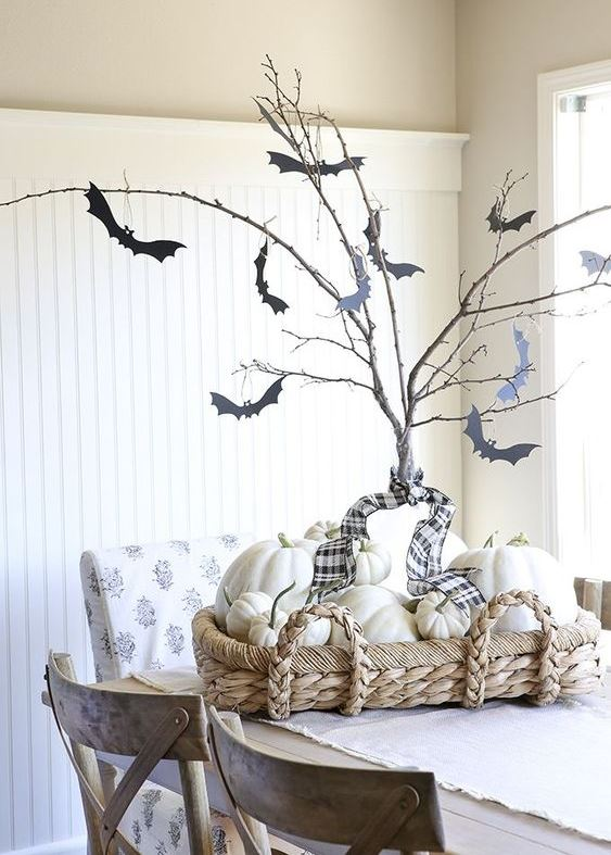 a rustic Halloween centerpiece of a basket with white pumpkins, a tree with a plaid ribbon and paper bats