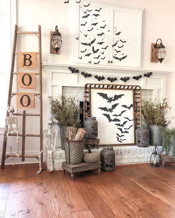 a rustic Halloween mantel with lots of bats, dried branches, jack-o-lanterns, skeletons, a ladder with letters