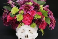 a skull with a bold floral arrangement in pink, red and green plus some leaves is a timeless idea for Halloween