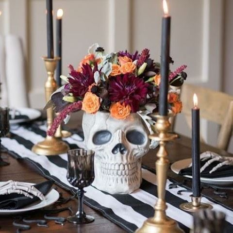 a skull with dark blooms and black candles in brass candleholders for a chic Halloween tablescape