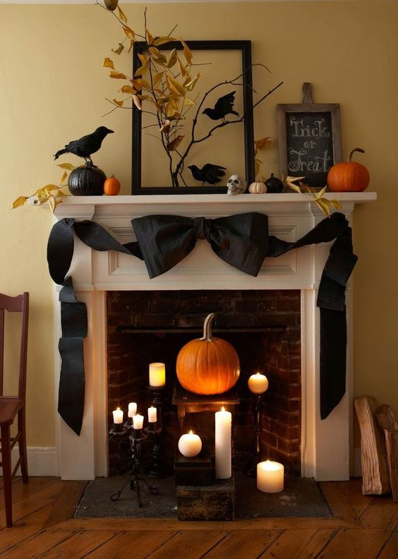 a sophisticated Halloween mantel with pumpkins, blackbirds, branches with leaves, a giant black bow and candles in the fireplace