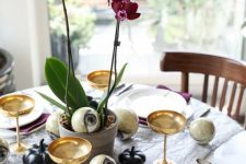 a spooky yet elegant Halloween centerpiece of purple potted orchids and some faux human eyes