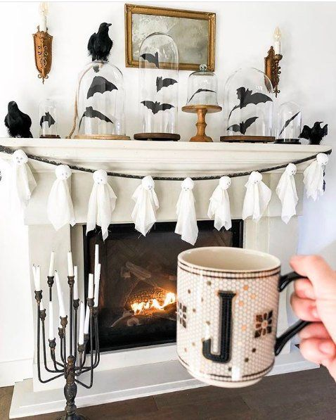 a stylish Halloween mantel with a ghost garland, bats in cloches and blackbirds is an elegant piece