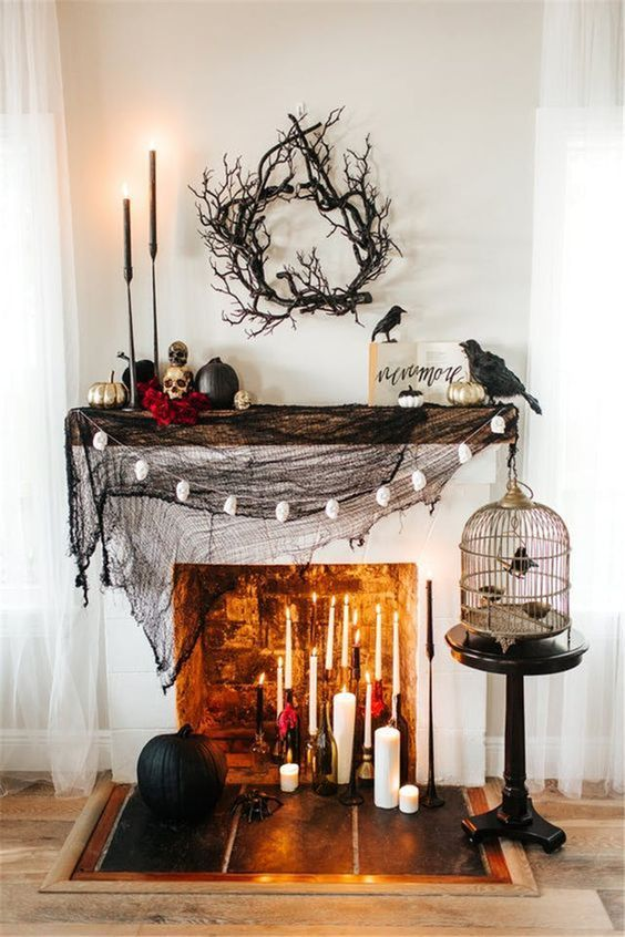 a stylish Halloween mantel with black spiderweb, lots of candles, skulls and black and gilded pumpkins plus blackbirds