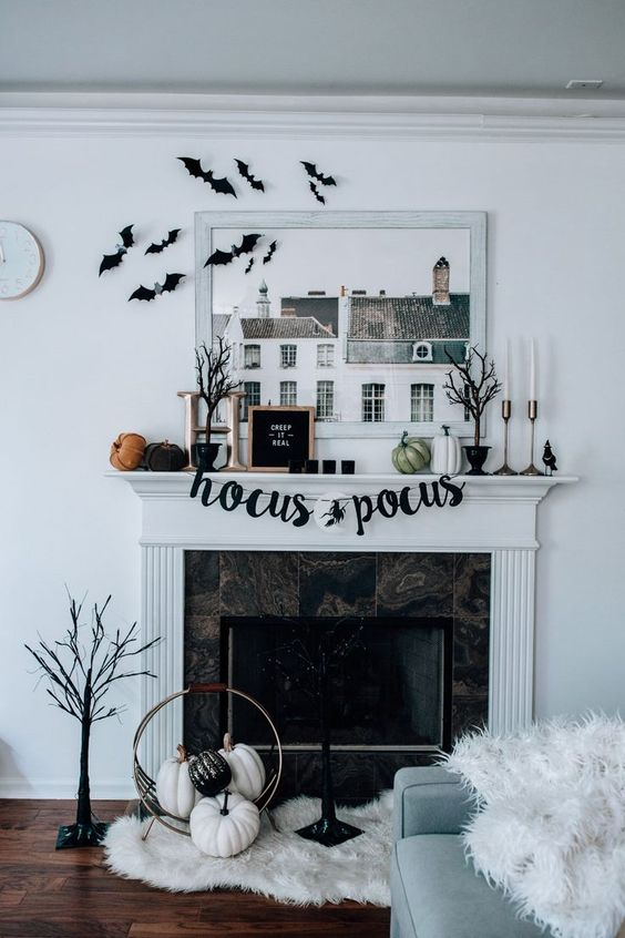 a stylish modern Halloween mantel with bats, pumpkins, signs, scary trees, candles and pumpkins on the floor