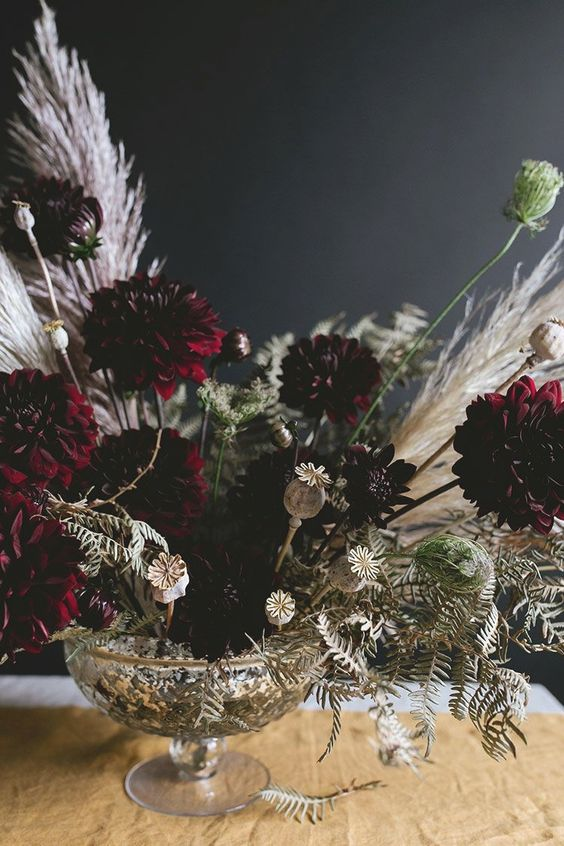 a super elegant Halloween centerpiece of a silver bowl and moody florals plus white dried herbs and greenery