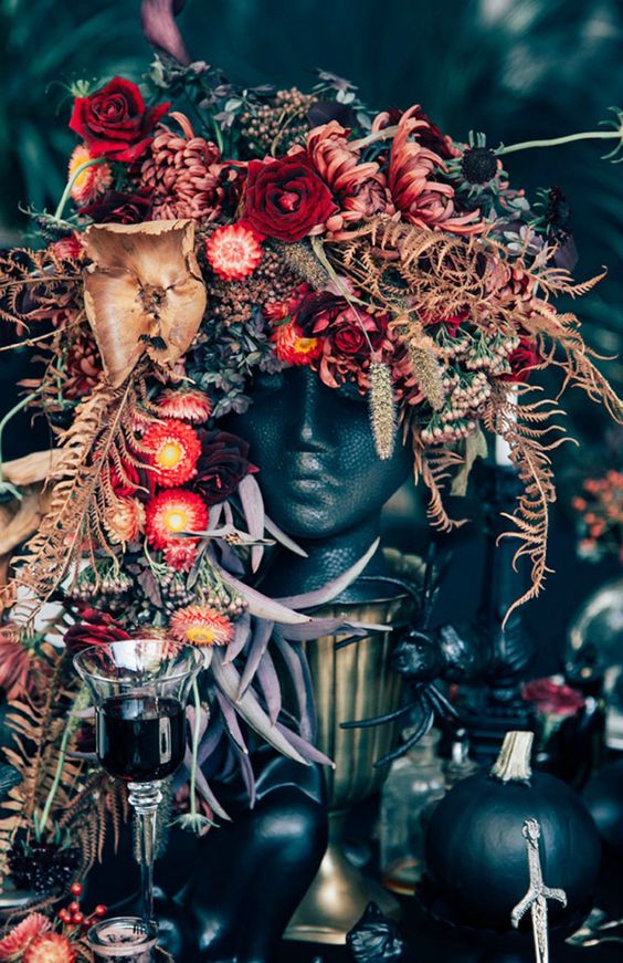a unique and lush Halloween centerpiece of a black human bust, dried leaves and greenery plus pink and red blooms