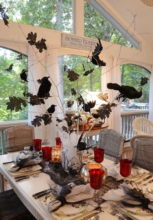 a vase with branches, faux leaves and crows plus candles around for a Halloween table setting