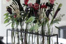 a very elegant Halloween centerpiece of a stand with test tubes, deep purple callas and burgundy blooms, greenery, feathers and skeleton hands