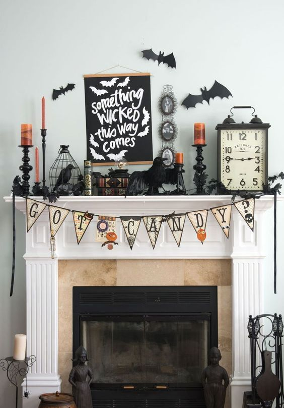 a vintage Halloween mantel with a bunting, blackbirds, orange candles, bars and vintage books and clocks